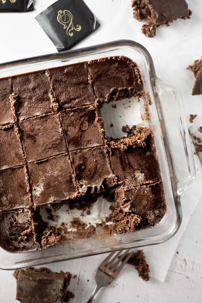 Overhead view of a square glass baking dish of after eight brownies with some pieces missing and scattered on the table