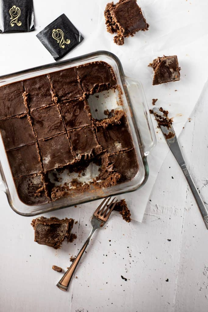 Overhead shot of after eight brownies in a square pan with some missing, a fork and after eight mints scattered on the table around the brownies