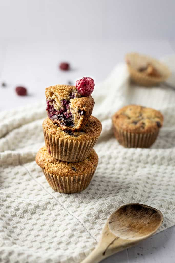 Three almond flour raspberry muffins stacked on top of each other, with the top muffin bitten into