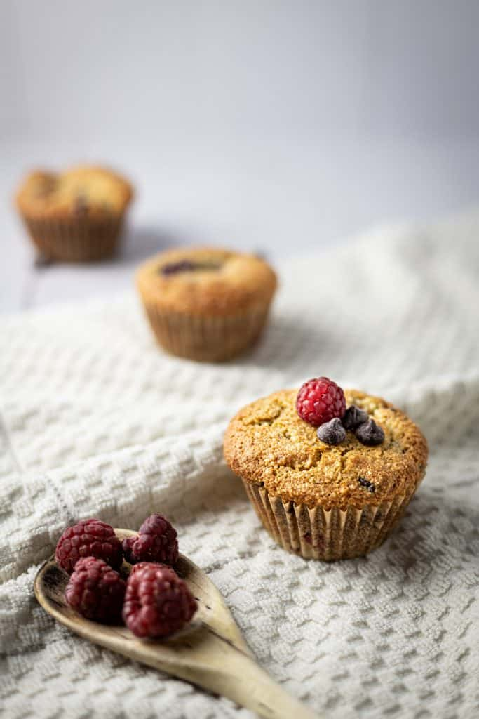 Three almond flour raspberry muffins in a trail, with a wooden spoon full of raspberries in the front