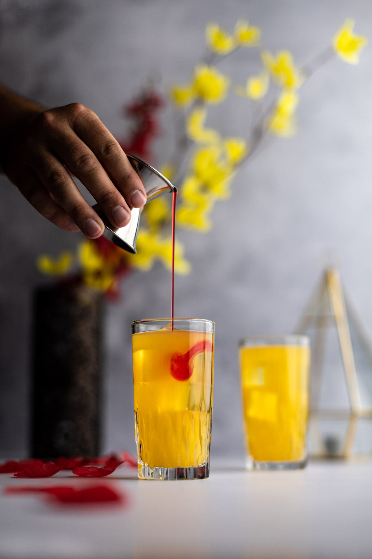 Hand holding a metal jigger with grenadine syrup being poured into an amaretto cocktail.