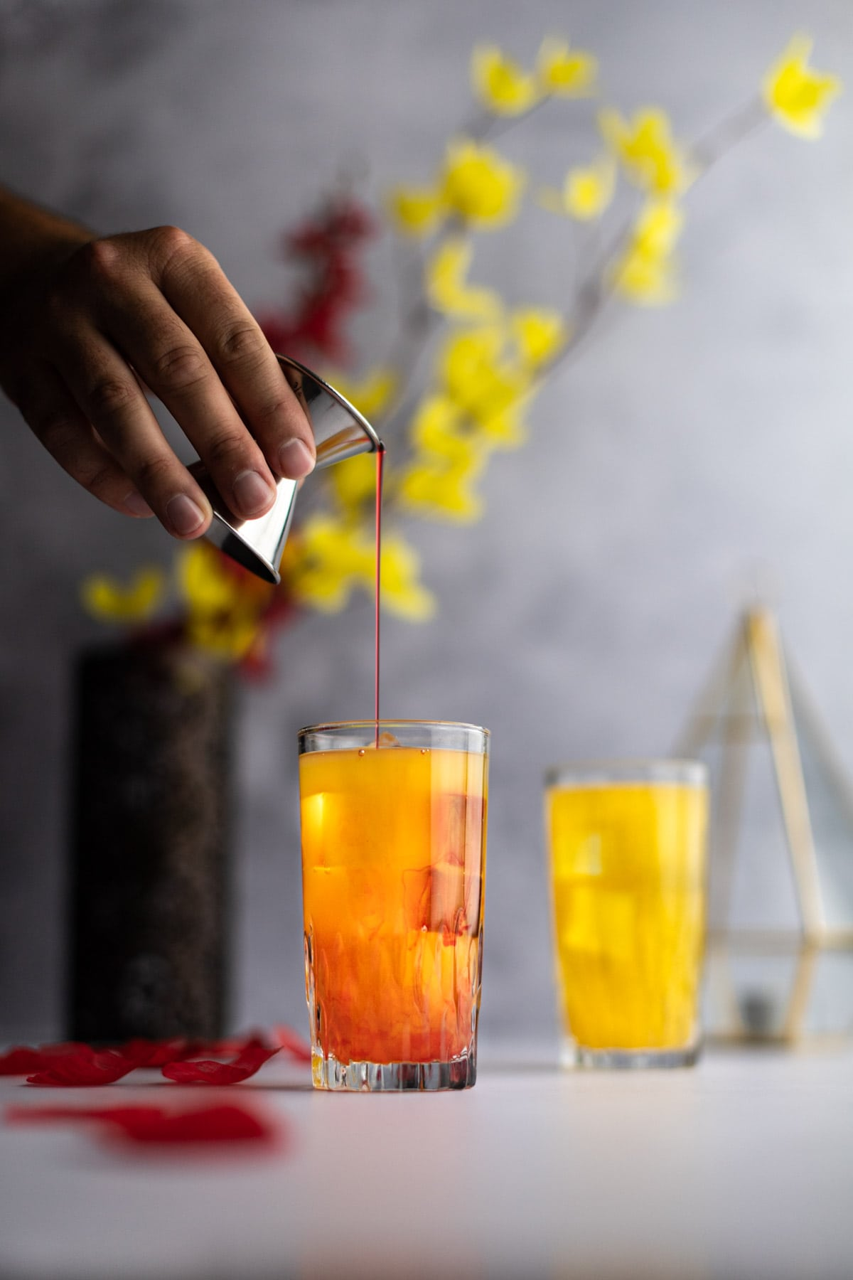 Grenadine syrup being poured into a yellow cocktail, half mixed with the peach nectar, red and yellow flowers in the background.