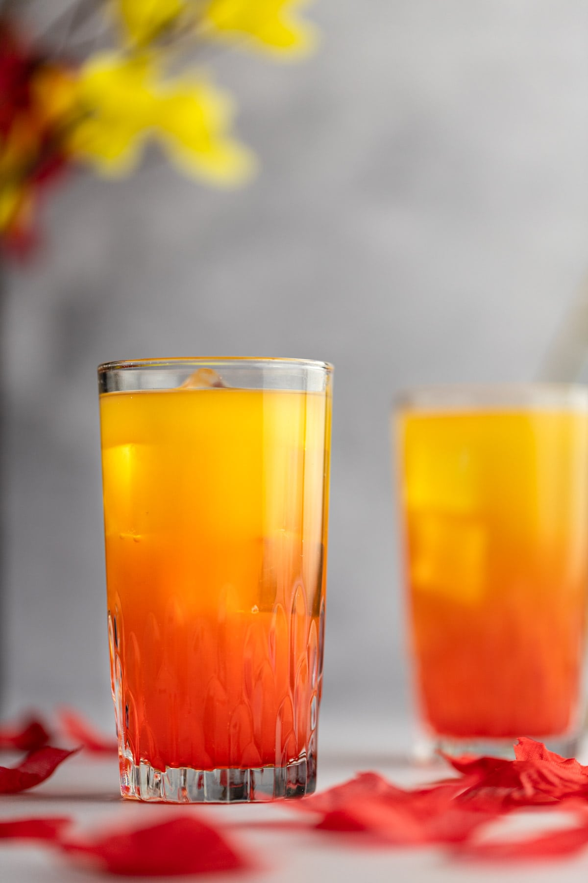 Close up of an amaretto sunrise cocktail, with rose petals scattered around the drink and flowers in the background.