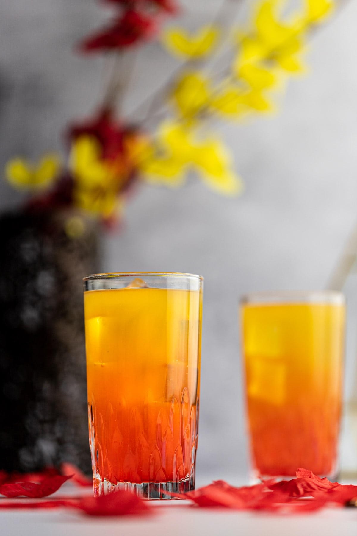 Two glasses of ombre amaretto sunrise cocktails, with red on the bottom and yellow on top, with yellow and red flowers in the background.