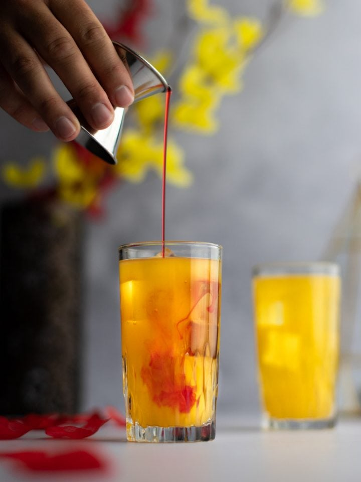Grenadine being poured into an amaretto sunrise cocktail, with rose petals scattered around and red and yellow flowers in the background.