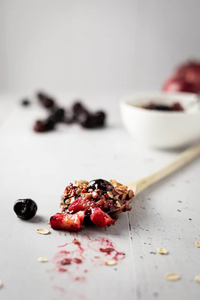 Close up view of a wooden spoon with a scoop of cherry and apple crumble on it with a bowl of crumble and a pile of cherries in the background