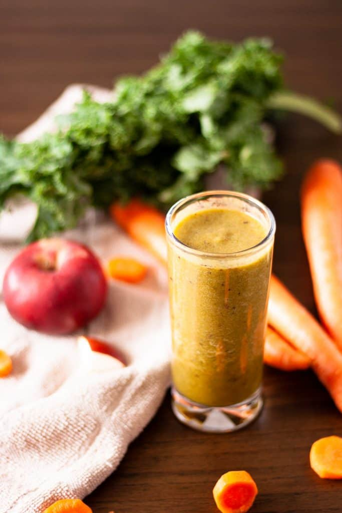 ¾ overhead view of an apple and carrot smoothie with carrots, kale and an apple around the glass, on a brown table