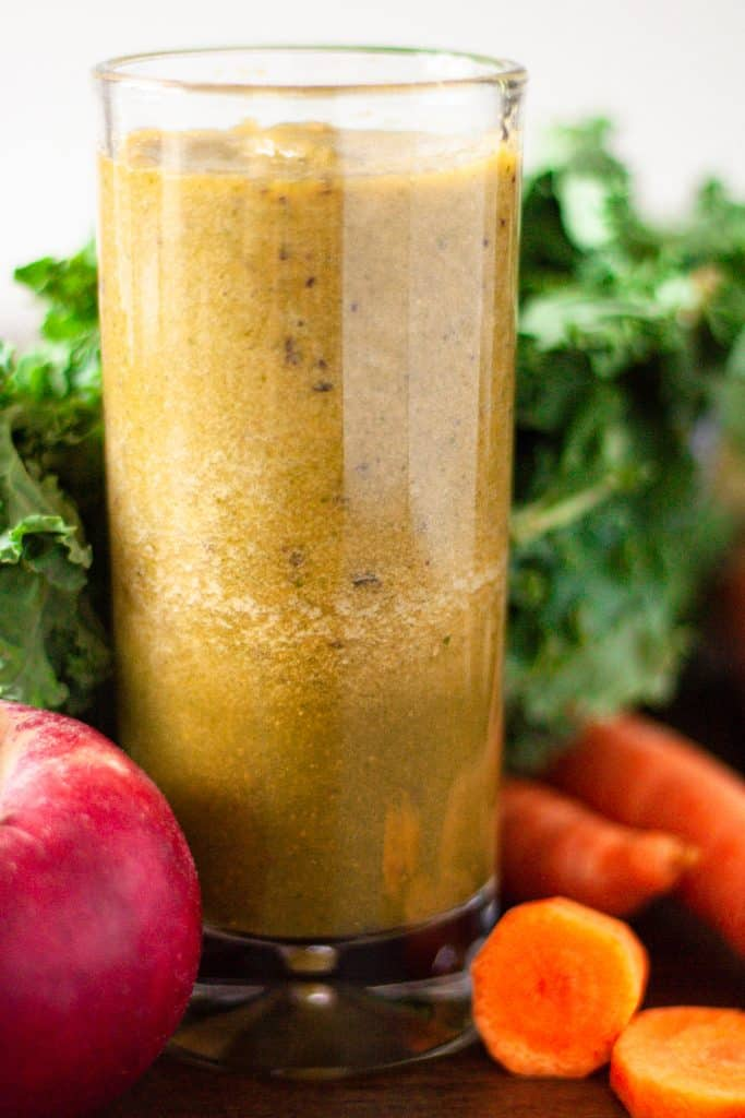 Up close, eye level view of a green kale, carrot and apple smoothie surrounded by an apple and carrots.