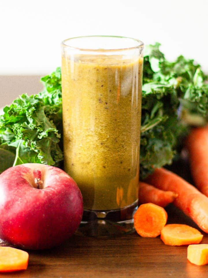 Tall glass of carrot, apple, kale and ginger smoothie with kale leaves, carrots pieces and an apple around the glass.