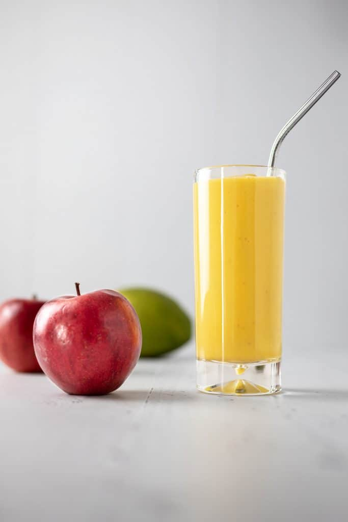 A tall glass of apple mango smoothie with a metal straw sticking out, and a couple apples and mango on the table beside it
