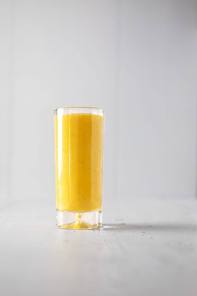 A tall glass of mango apple smoothie on a plain table, with a plain background