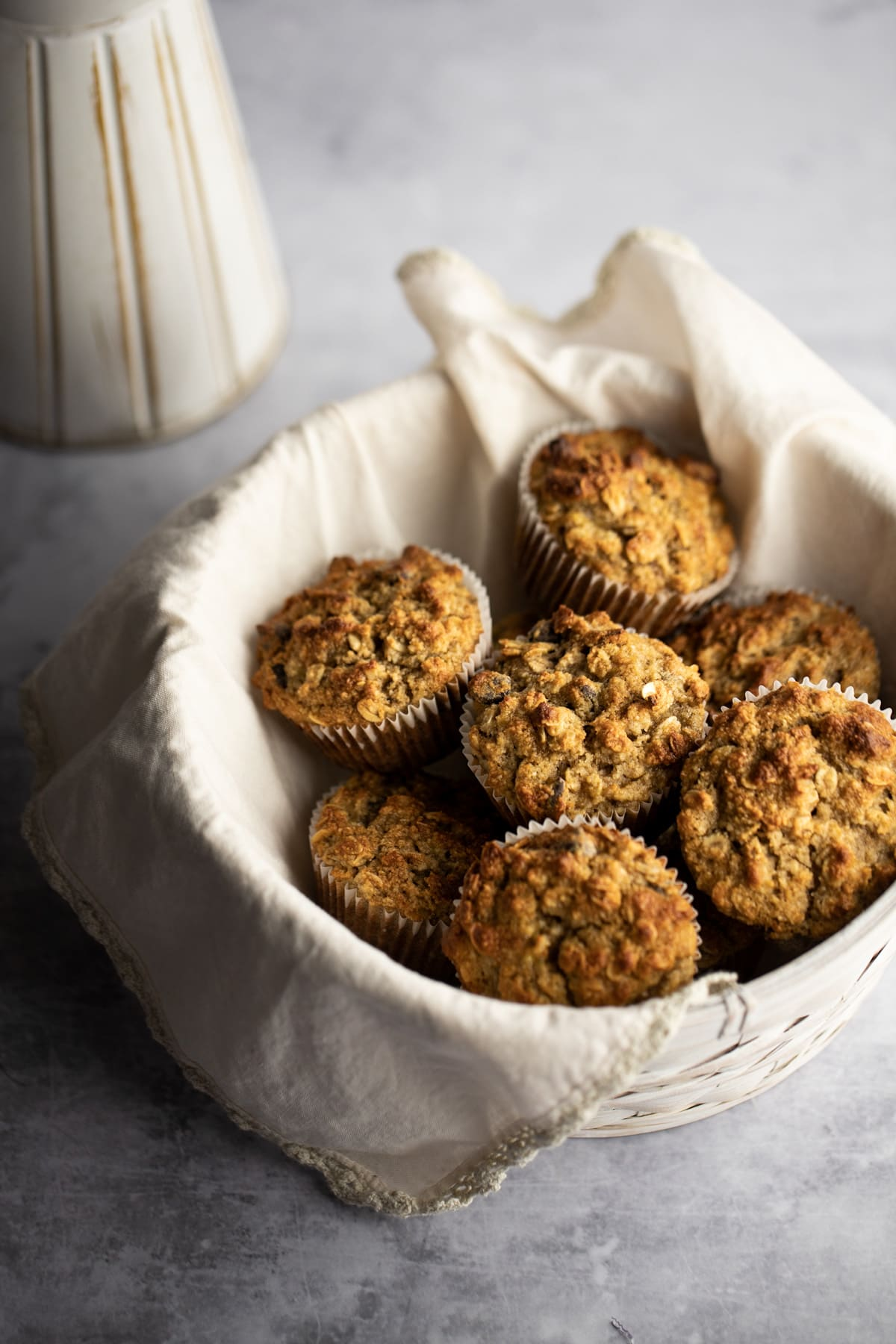 A white basket with a beige napkin filled with muffins, on a grey table.