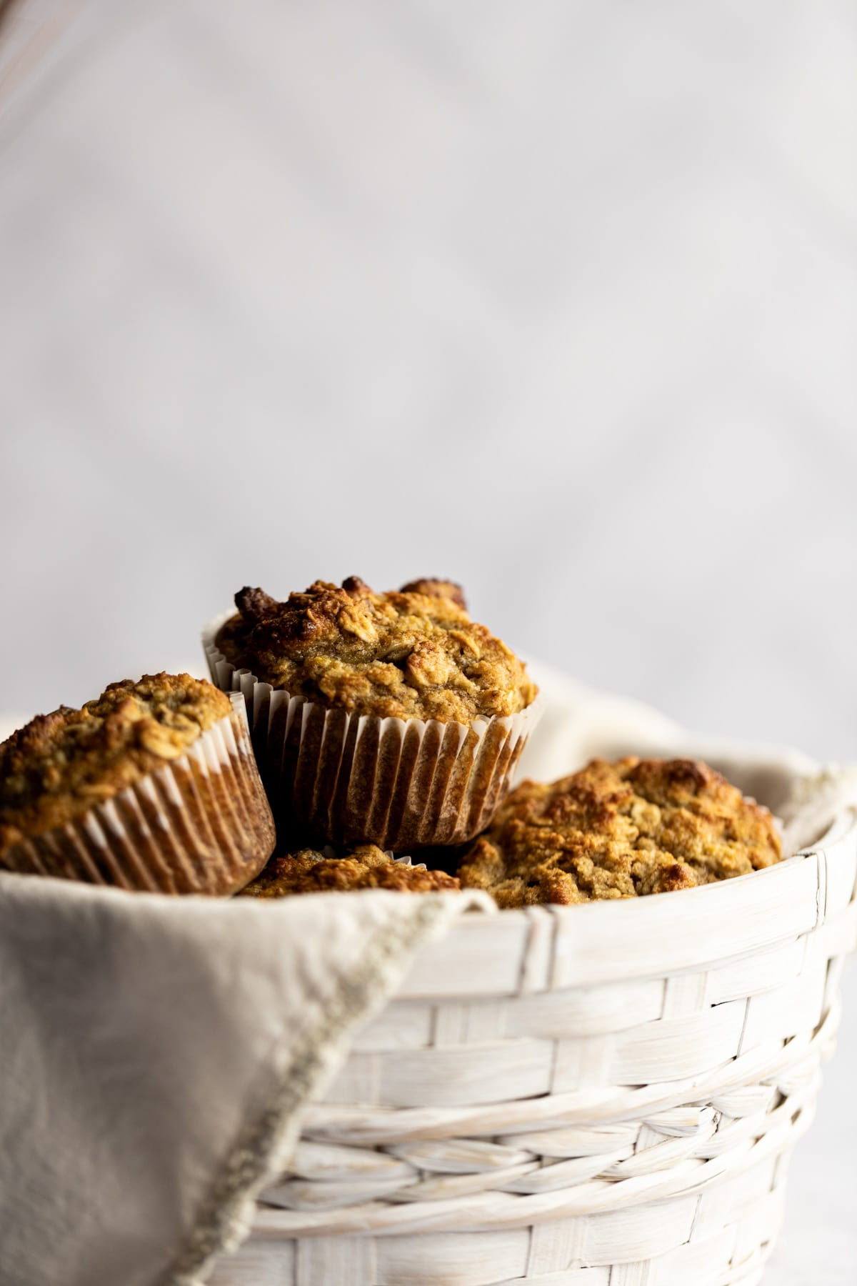 Up close shot of golden almond flour muffins in a white basket.