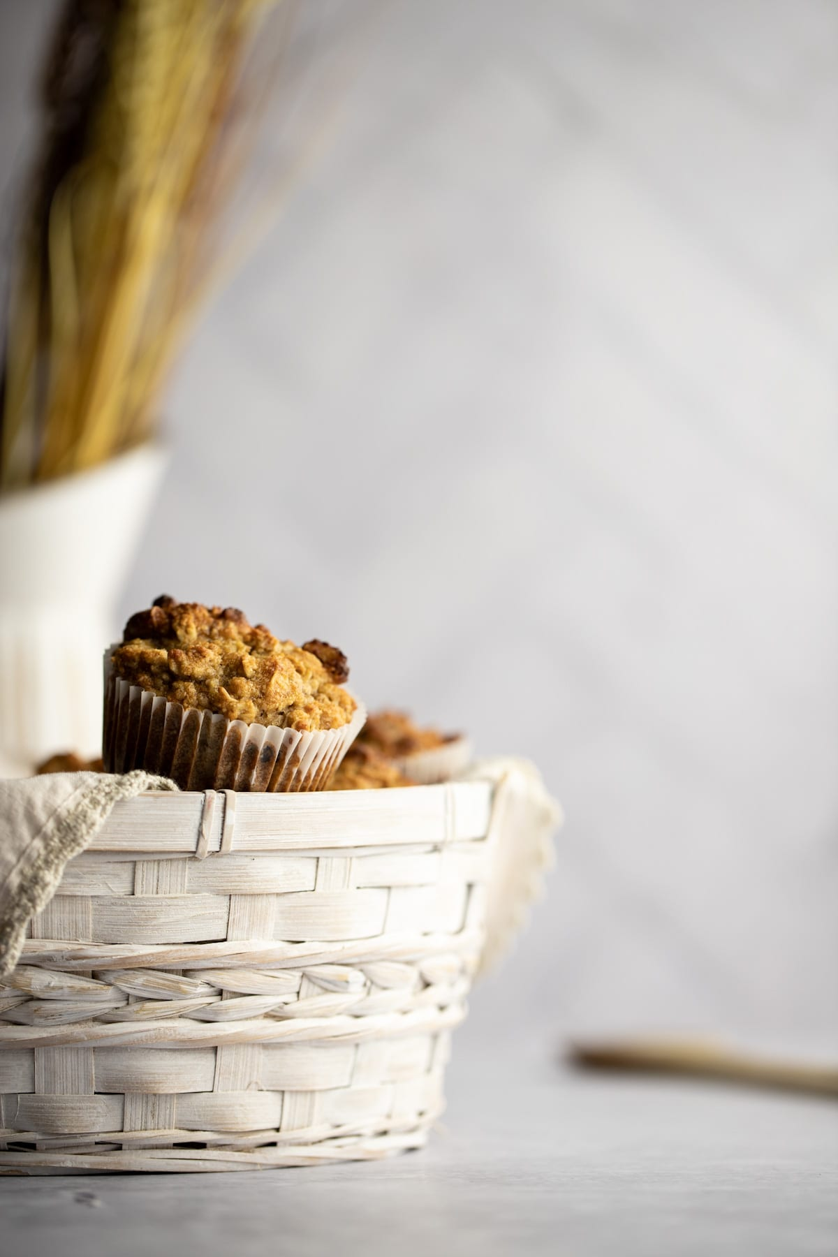 Banana almond flour muffins overflowing from a basket, with a white jug with wheat in it in the background.
