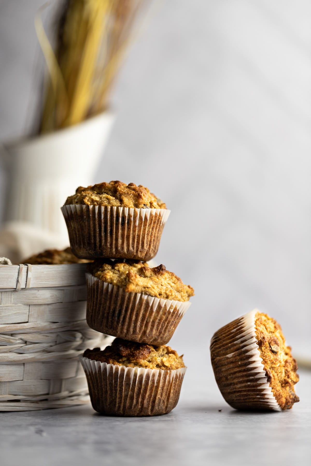 A stack of three almond flour banana muffins leaning against a basket, with one muffin tipped on its side lying beside the stack.