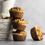 A stack of banana almond flour muffins leaning against a white basket, one muffin lying on its side beside the other muffins.