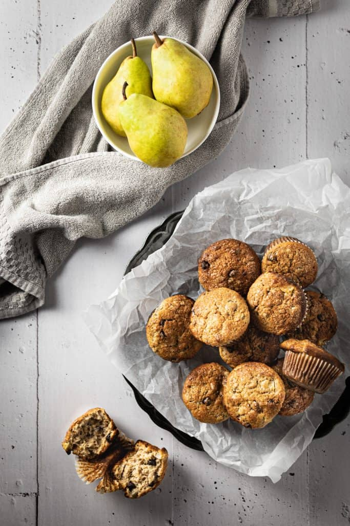 Overhead view of a bowl of muffins, a bowl of pears and a cut open muffin