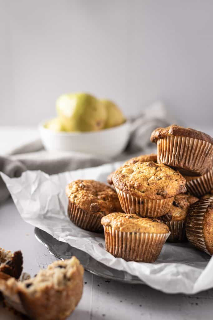 A side angle view of a plate of pear banana muffins with pears in the background
