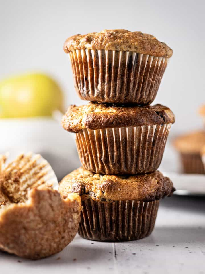 Three banana and pear muffins stacked on top of each other, with a half eaten one lying in front