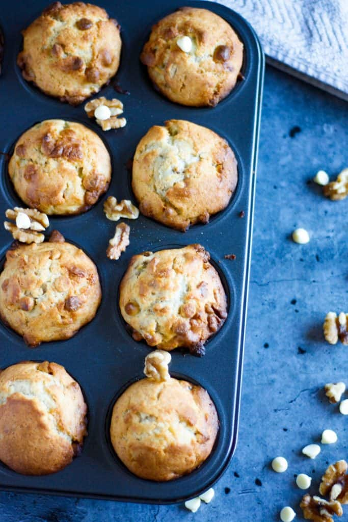 an overhead view of a muffin tin filled with banana white chocolate muffins