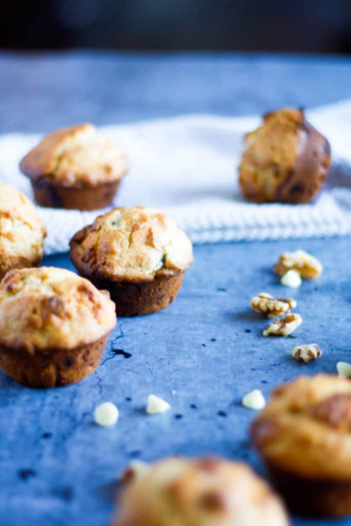 a side view of banana and white chocolate muffins on the table with a tablecloth in the background