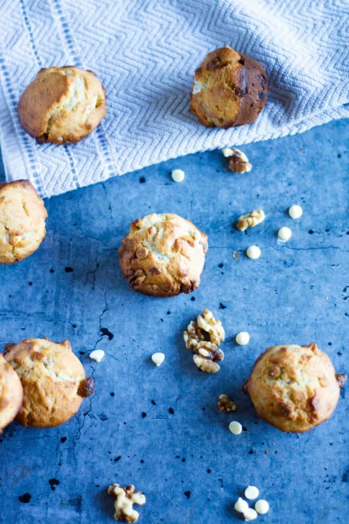an overhead view of white chocolate banana muffins scattered on a blue background