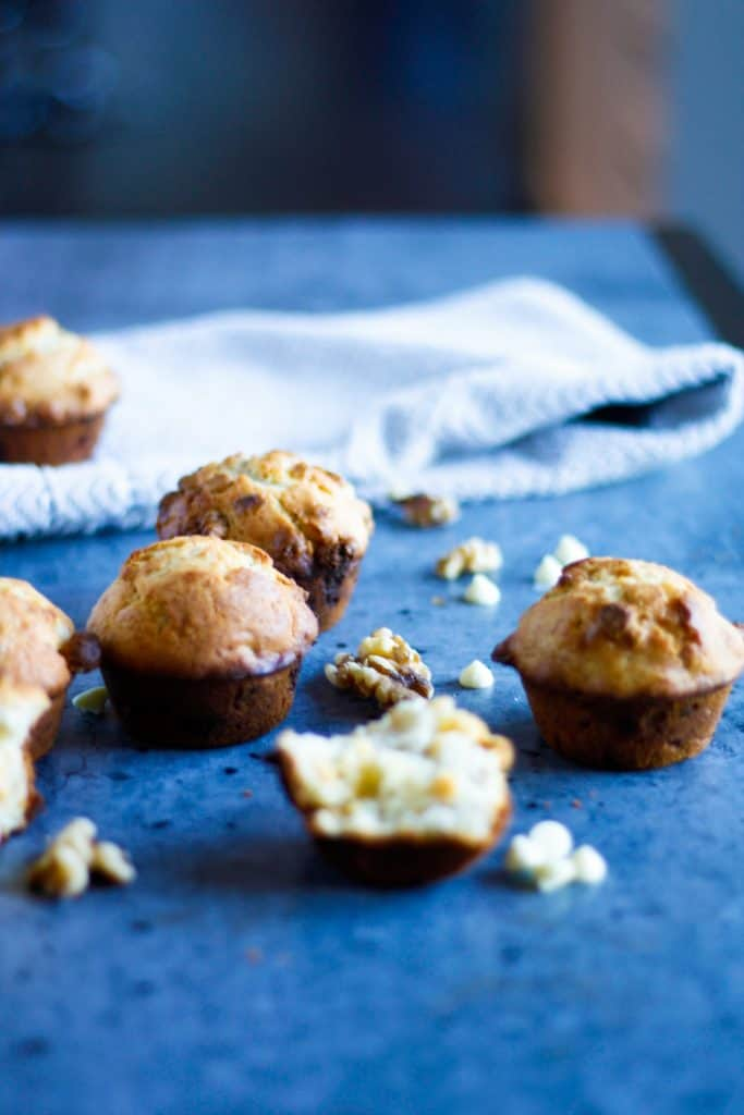 banana white chocolate muffins spread out on a table, with one muffin split in half