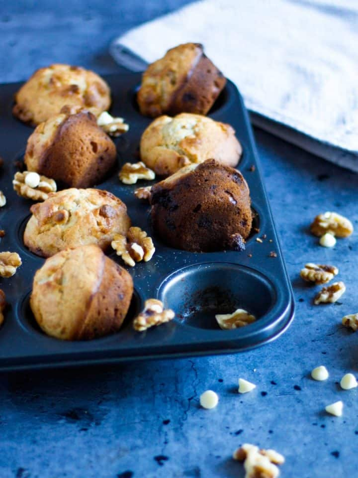 a tin filled with banana white chocolate muffins, scattered with white chocolate chips and walnuts