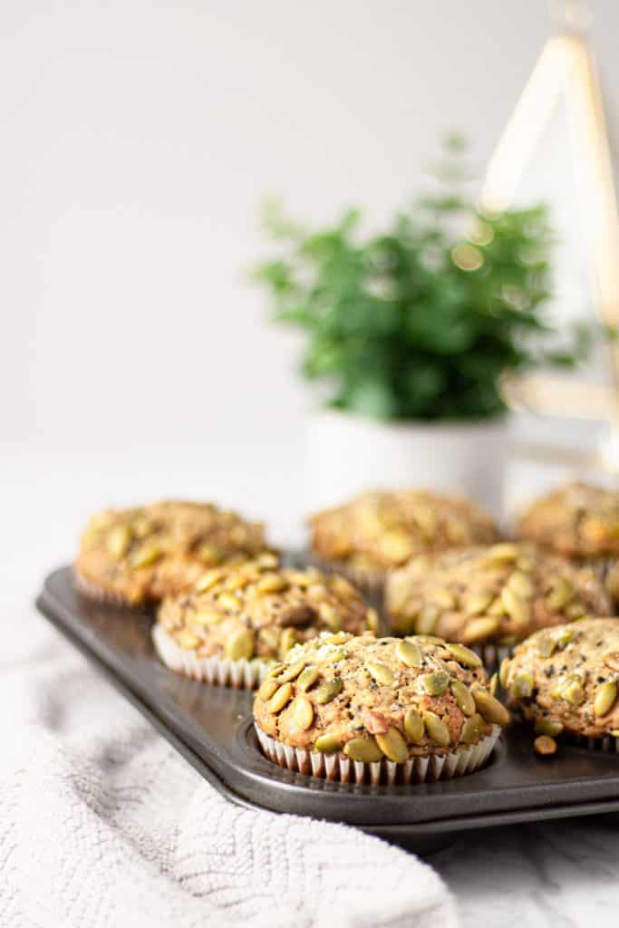 Muffin tin full of black sesame muffins sitting on a light grey towel with a small green plant in the background