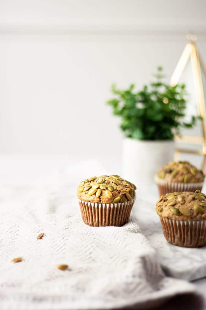 Three black sesame muffins on a light grey towel with a green plant in the background and scattered pumpkin seeds in the foreground
