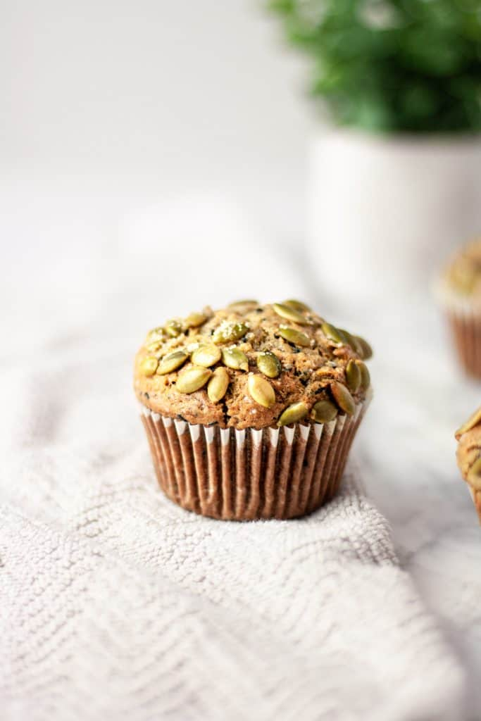 Up close view of a black sesame muffin with pumpkin seeds and turbinado sugar on top