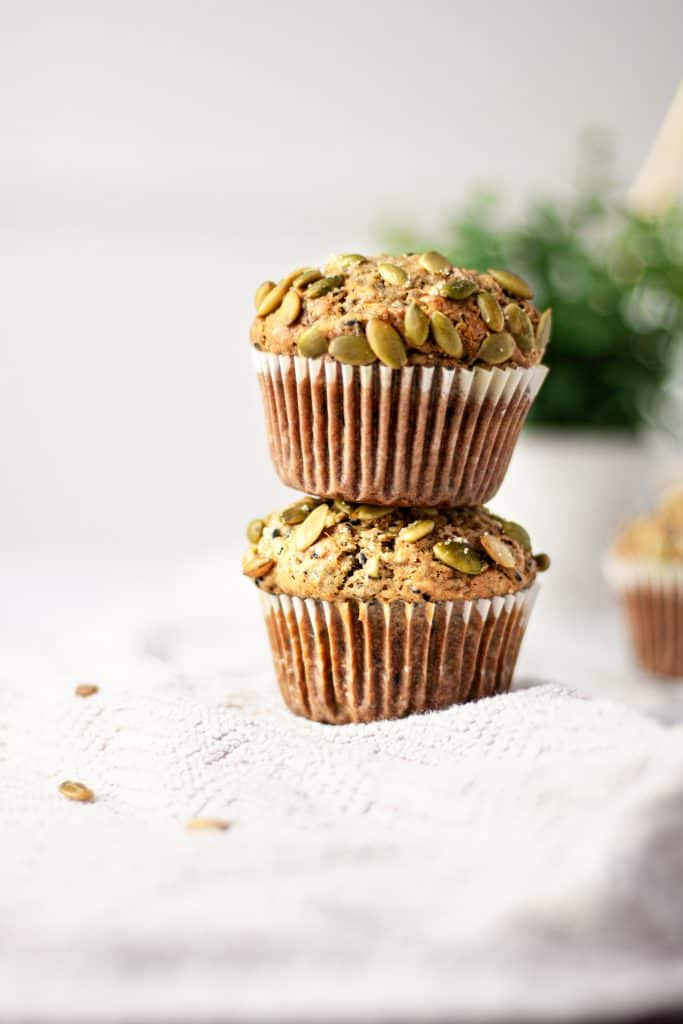 Two black sesame muffins stacked on top of each other with pumpkin seeds scattered on the side