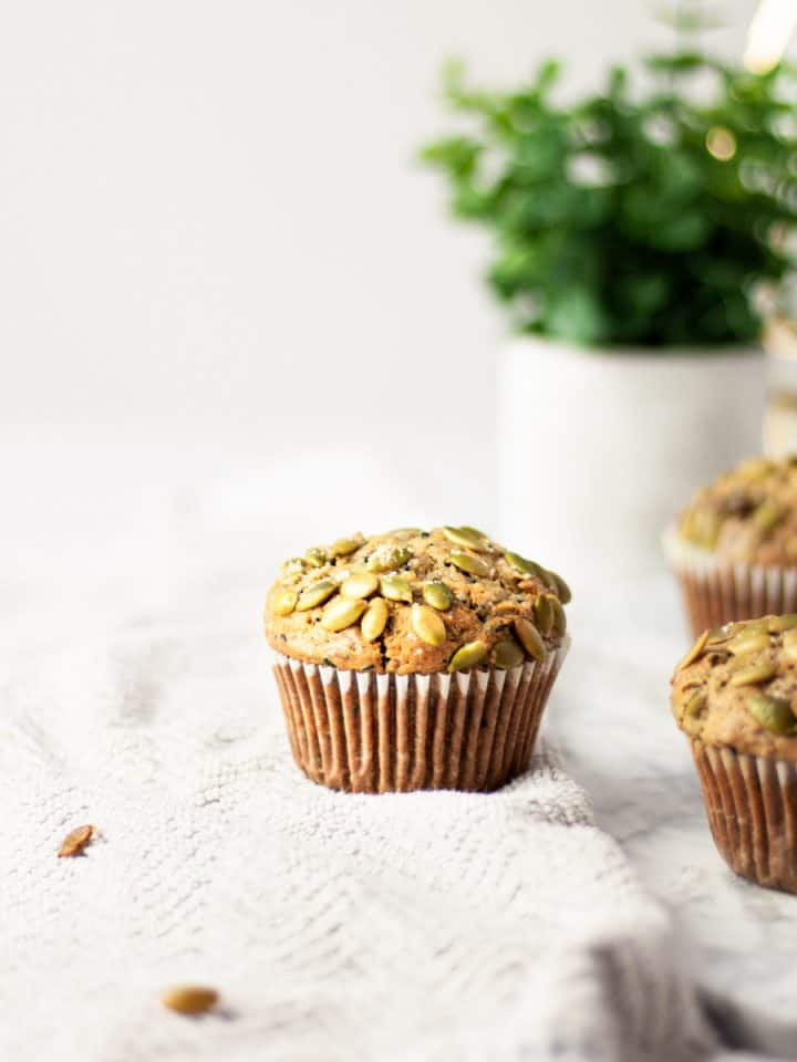 Three black sesame muffins on a light grey towel with a green plant in the background.