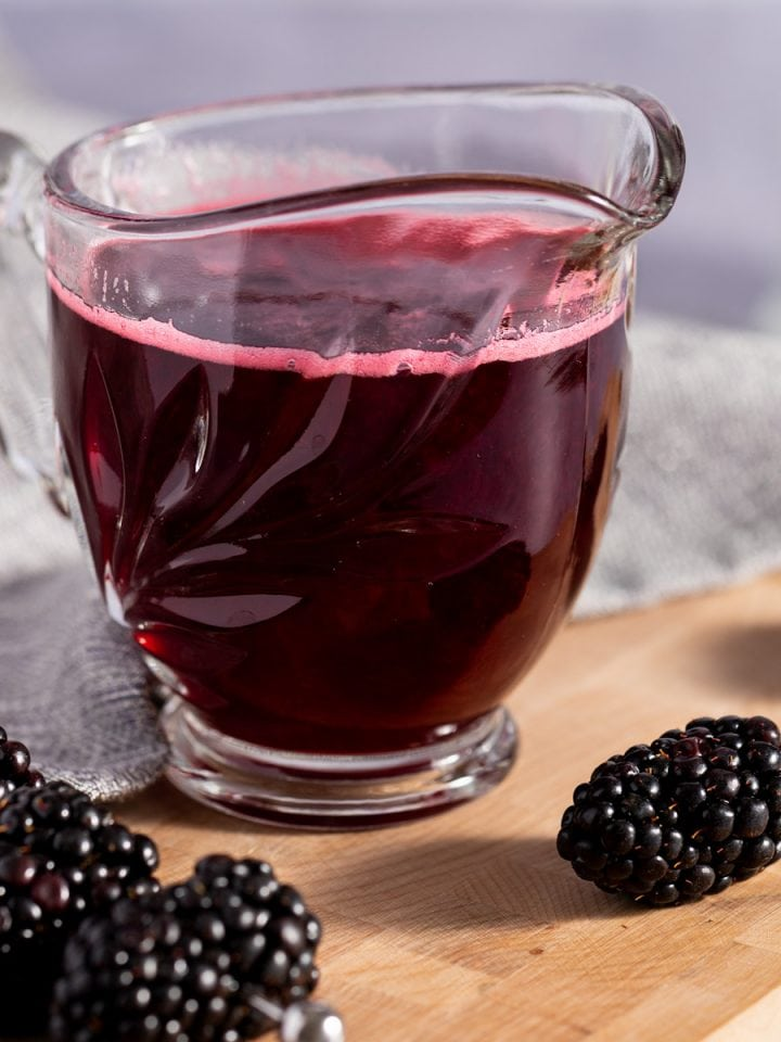 Blackberry simple syrup in a small glass container, next to fresh blackberries, on a wooden board with a grey napkin in the background.
