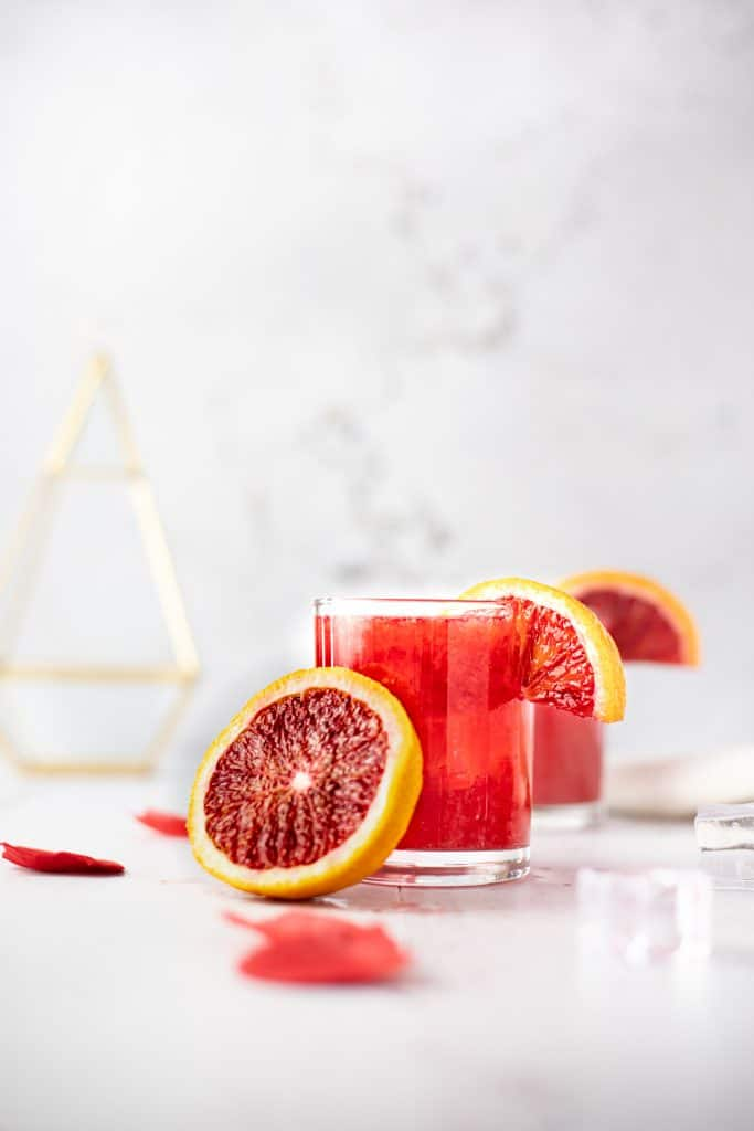 A glass of blood orange whiskey sour with half a blood orange leaning against the glass and rose petals scattered on the table