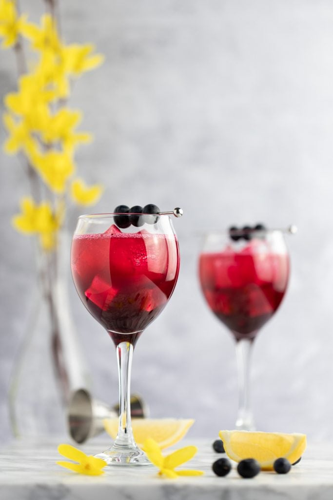 Two blueberry gin cocktails with blueberries as garnish, on a marble table next to lemon slices and yellow flowers.