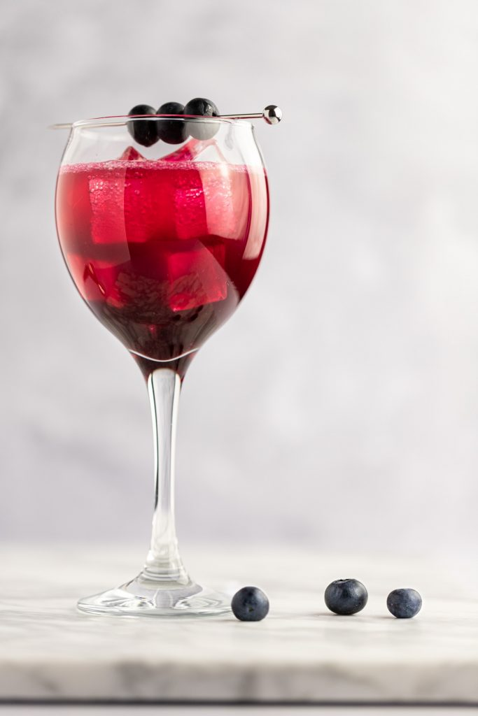 A single glass of blueberry cocktail on a white marble board, with three fresh blueberries beside it.