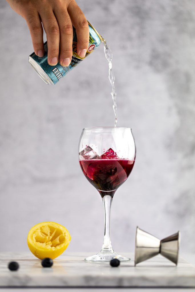 A hand holding a can of club soda being poured into a half filled blueberry cocktail with ice, next to a metal jigger, squeezed lemon and blueberries.