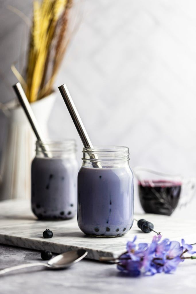 Two blueberry milk tea jars on a marble board, next to a jar of blueberry syrup, blueberries and a bunch of blue flowers.
