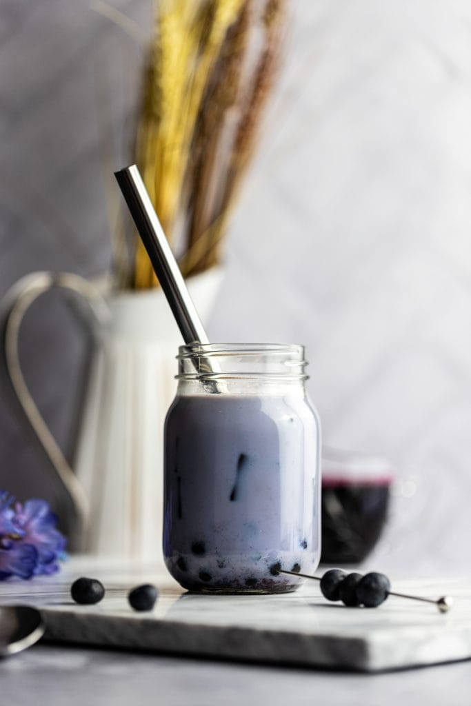 A shadowy photo of a blueberry bubble tea with boba, syrup and a white jug with wheat and purple flowers in the background.
