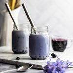 Two blueberry milk teas on a marble board next to blueberries, syrup and purple flowers.