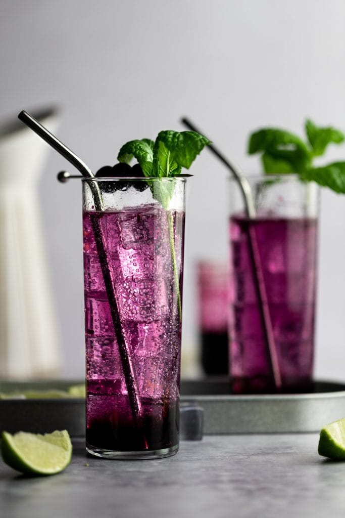 A couple of purple blueberry mojitos with mint and blueberries as garnish.
