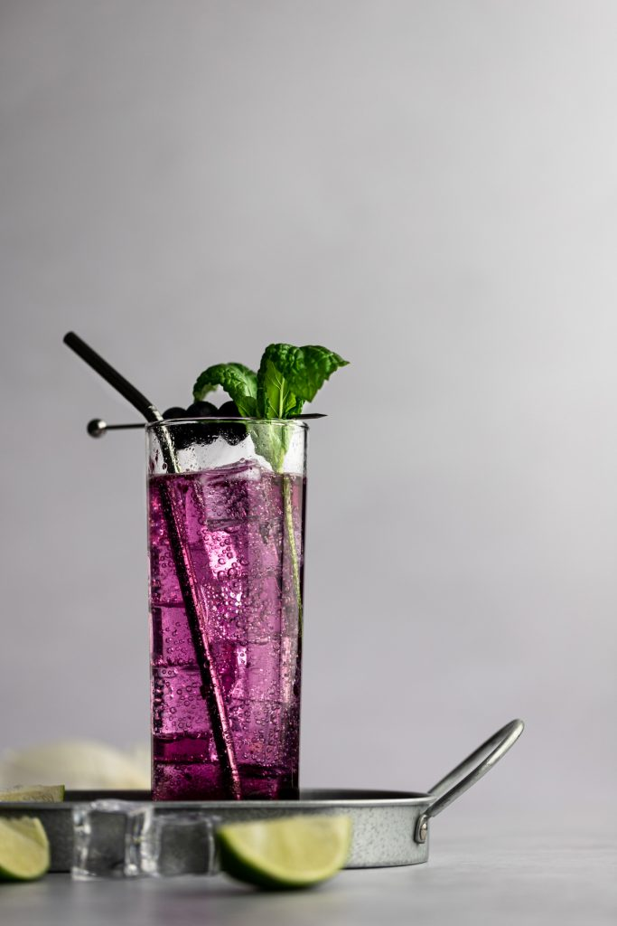 A blueberry mojito of a metal serving tray, next to ice cubes and lime slices.