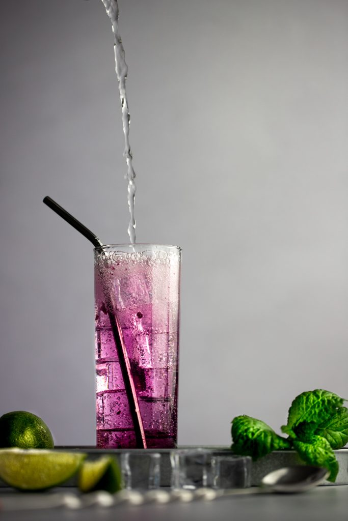 Action shot of club soda being poured into finished blueberry cocktail.