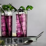 A couple of blueberry mojitos with mint and blueberry garnish, lined up on a metal serving tray.