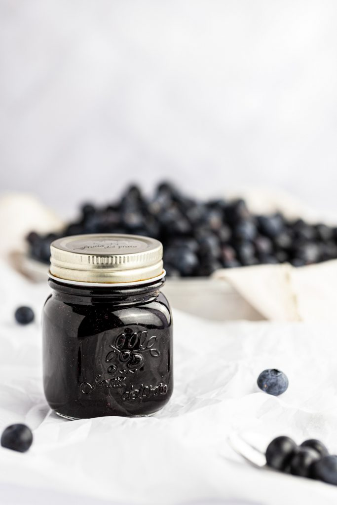 A glass jar of blueberry syrup with a bowl filled with fresh blueberries in the background.