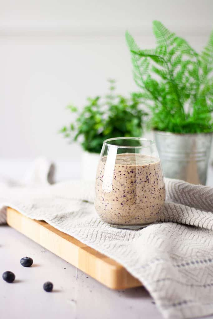 Glass of blueberry tahini smoothie on a light brown hand towel with a plant in the background and blueberries in the foreground