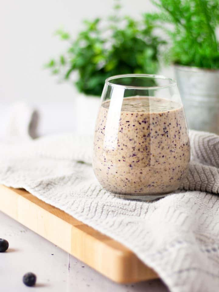 A glass of blueberry tahini smoothie on a light brown hand towel with a plant in the background and scattered blueberries in the foreground