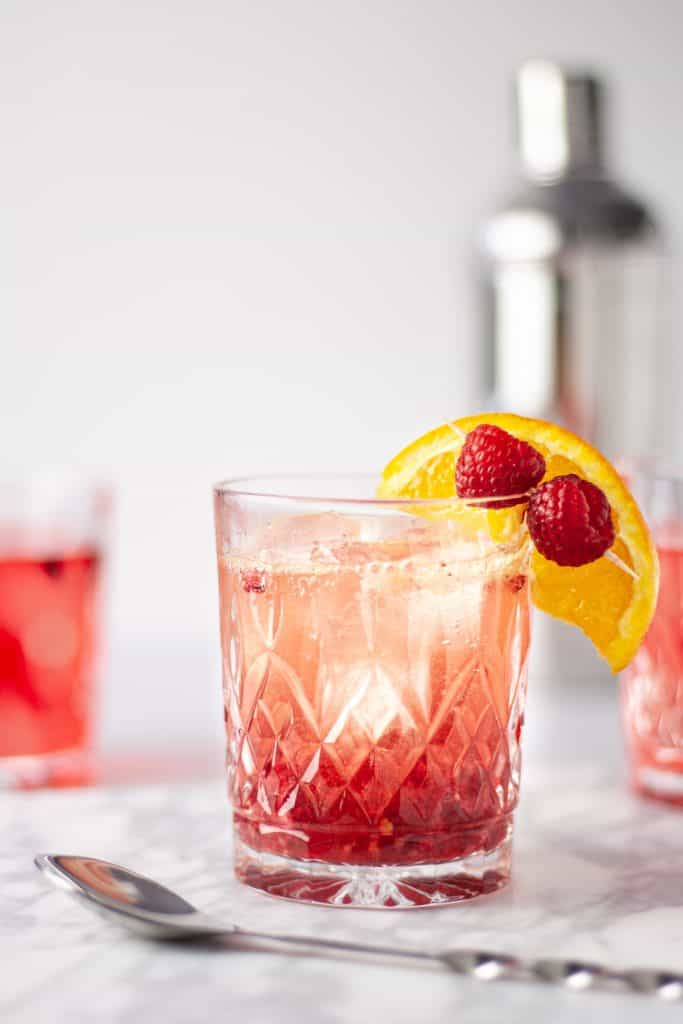 A glass of bourbon raspberry cocktail on a white marble board with a couple other cocktail and a long metal stirring spoon in front.
