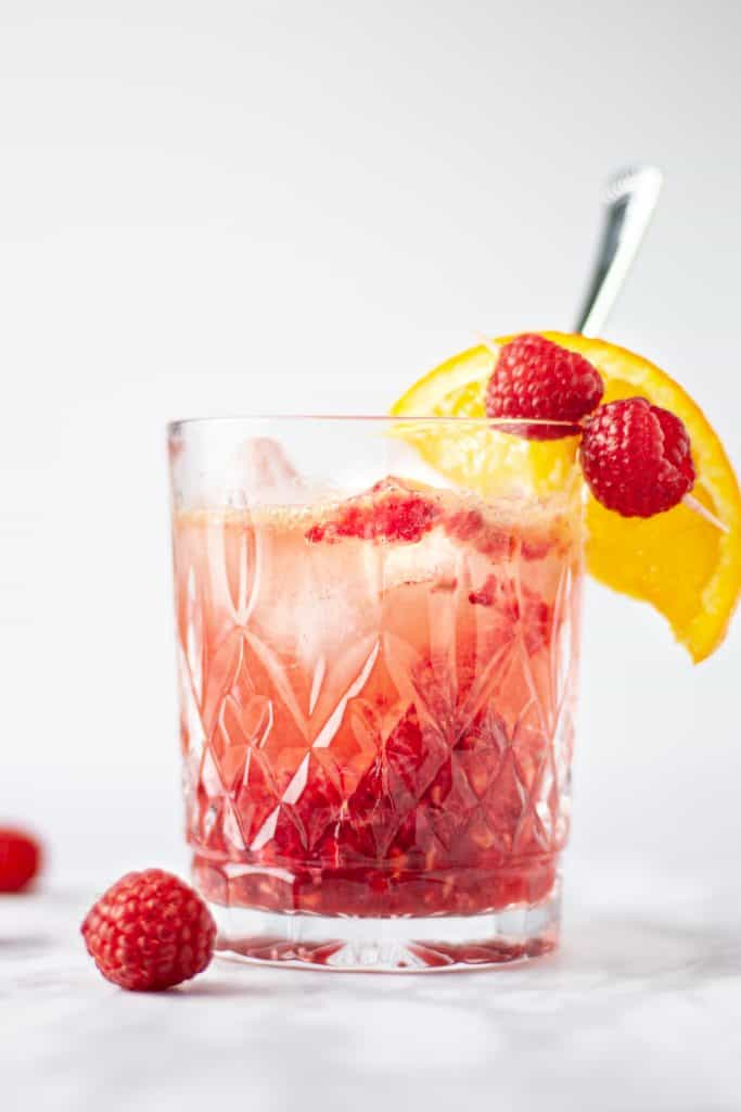 Eye-level view of a glass of bourbon raspberry cocktail with a couple raspberries and an orange slice as garnish.